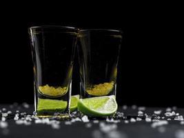 två skott av tequila guld med kalk foto