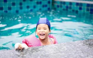 ung asiatisk flicka som leker i en pool foto
