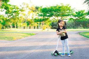 ung asiatisk tjej rider på skoter i parken foto