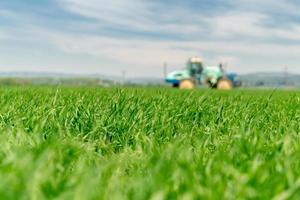 högt fält av gräs med suddig traktor foto
