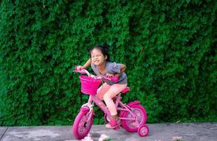 ung asiatisk flicka som cyklar foto