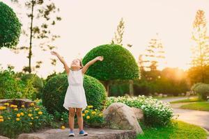 ung flicka öppnar armarna mot himlen på sommaren foto