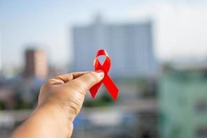 rött band i handen för världshjälpdag