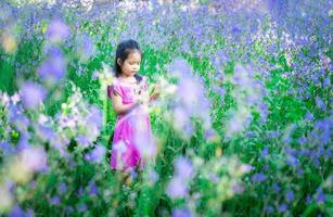 glad liten asiatisk flicka i blommaträdgård foto