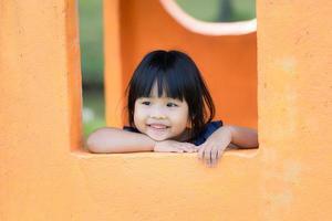ung asiatisk tjej i fönstret tycker om lekplats foto