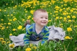 glad liten pojke som ligger på en filt utomhus foto