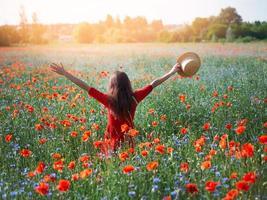 ung vacker kvinna med upphöjda armar i våren vallmo-fältet foto
