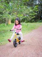 lilla flickan lär sig att rida balanscykel i parken foto