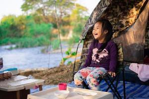 ung flicka sitter på en campingplats, ler