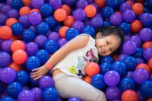 ung asiatisk tjej som spelar i bouncy ball pit foto