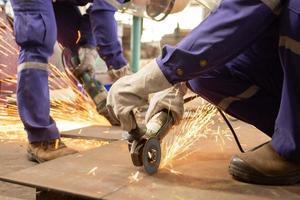 två manliga arbetare som skär metallplåtar foto