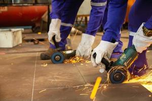 två arbetare klippte metallplåtar med elektrisk kvarn foto