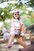 ung asiatisk flicka på gungbräda foto