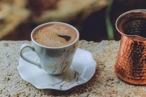 morgonkaffe i keramisk kopp och maträtt foto