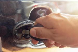 närbild av handen som sätter in en nyckel i bildörren foto