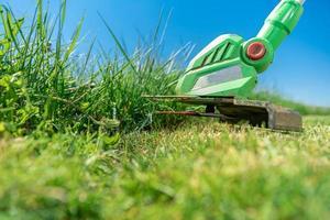 elektrisk gräsklippare skär gräs foto
