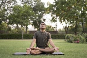 man gör yoga utomhus foto