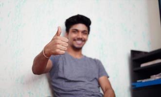 ung asiatisk pojke som visar tummen upp foto