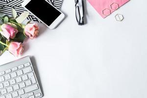 platt låg med tangentbord, telefon, blommor och glasögon