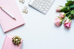 platt läge av kontorsskrivbord med rosa blommor, anteckningsbok och present