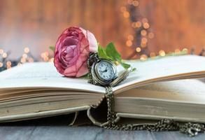 öppen bok med fickur och blomma