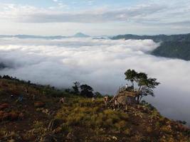 människor med utsikt över dimmiga kullar foto
