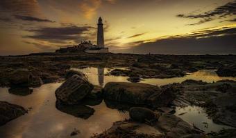 fyr på stenig kust under solnedgången foto