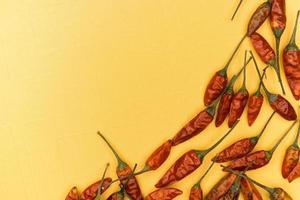 röd torkade chilipeppar på gul bakgrund foto