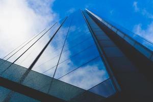moln och blå himmel återspeglas i byggnadsfönster foto