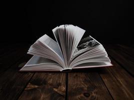 öppen bok på mörk bakgrund foto