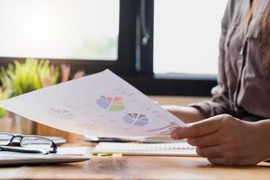 närbild av affärskvinna som tittar på diagram foto