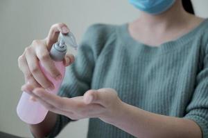kvinna som applicerar alkohol antiseptisk gel och bär ansiktsmask foto
