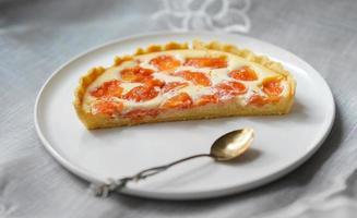 tårta med fruktskivor på keramisk platta foto