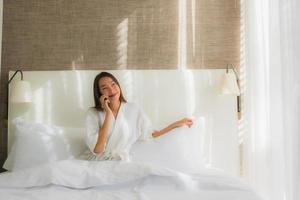 asiatisk kvinna med smartphone på sängen foto