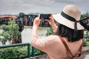 turist tar ett fotografi av sightseeing nära bron i Thailand foto