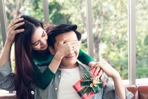 kvinna överraskar pojkvän med present till alla hjärtans dag foto