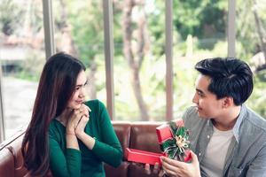 man överraskar flickvän a med gåva foto