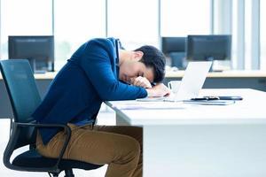 ung asiatisk affärsman som tar en tupplur på jobbet foto