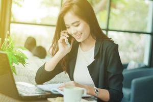ung asiatisk professionell kvinna använder sin mobiltelefon på jobbet foto