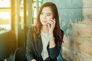 en ung professionell asiatisk kvinna använder sin telefon på sitt kontor foto