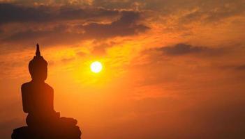 silhuett av Buddhastatyn vid solnedgången foto