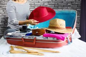 ung kvinna som packar kläder för resor foto