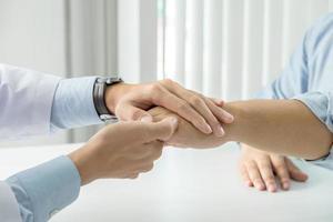 närbild av läkare vidrör patientens hand för stöd foto