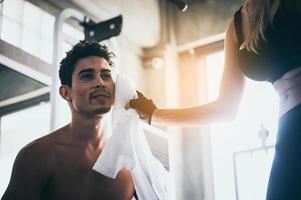 kvinna torkar svett från mans ansikte foto