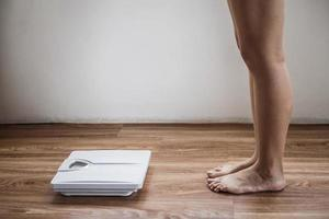 kvinnliga nakna fötter närmar sig skalan foto