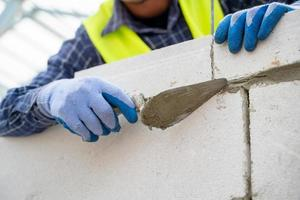 detaljerat skott av en byggnadsarbetare som applicerar gips på tegelväggen foto