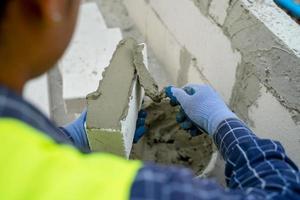 beskuren skott av en byggnadsarbetare som applicerar gips på en tegel foto