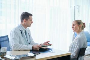 läkare diskuterar vård med patienten foto