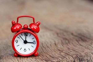röd väckarklocka på träbakgrund foto