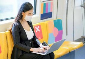 ung affärskvinna som tar tåget till jobbet foto